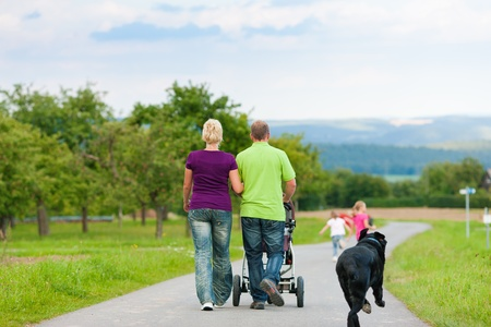 Family with three children (one baby lying in a baby buggy) walking down a path outdoors, two kids are running ahead, there is also a dog photo