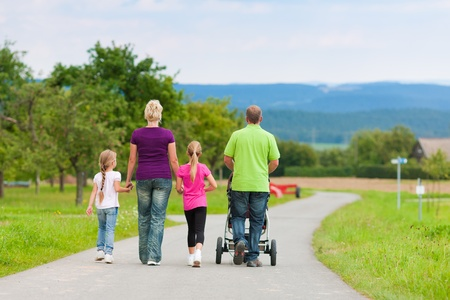 Family with three children (one baby lying in a baby buggy) walking down a path outdoors photo