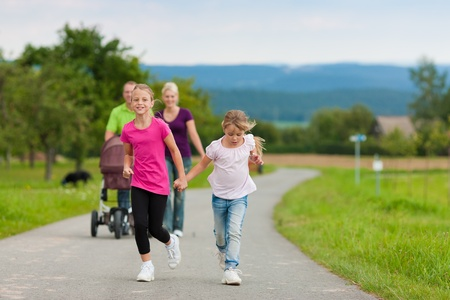 family walking: Family with three children (one baby lying in a baby buggy) walking down a path outdoors, two kids are running ahead, there is also a dog Stock Photo