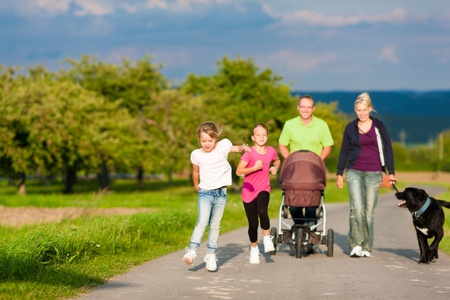 Family with three children (one baby lying in a baby buggy) walking down a path outdoors, two kids are running ahead, there is also a dog Stock Photo