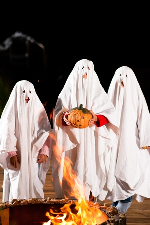 Three very, very scary spooks - kids dressed as ghosts - on Halloween or for carnival or a costume party in front of a fire; FOCUS IS ON PUMPKIN photo