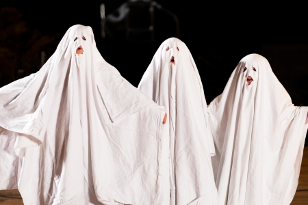 ghosts: Three very, very scary spooks - kids dressed as ghosts - on Halloween or for carnival or a costume party Stock Photo