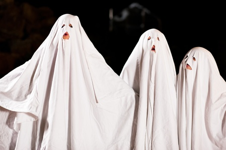 Three very, very scary spooks - kids dressed as ghosts - on Halloween or for carnival or a costume party Stock Photo