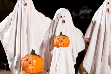 Three very, very scary spooks - kids dressed as ghosts - on Halloween or for carnival or a costume party, FOCUS IS ON PUMPKIN photo