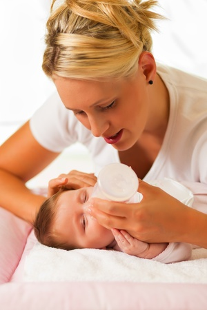 Mother is feeding her baby with a bottle; very tranquil scene   photo
