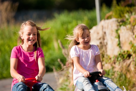 amounts: Two sisters with toy cars driving them down a hill having awesome amounts of fun