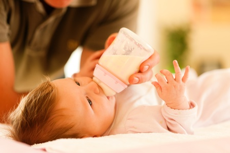 feed up: Father is feeding his baby with a bottle; very tranquil scene