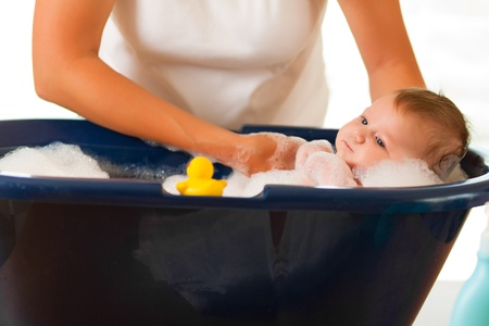 midwife: Mother is bathing her baby (just hands) Stock Photo