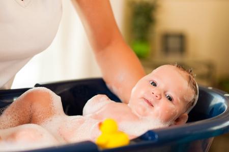 personas banandose: Madre es bañar a su bebé (manos sólo)