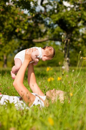 Mother playing with her baby on a great sunny day in a meadow with lots of green grass and wild flowers photo