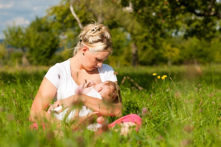 cradling: Mother cradling her baby on a great sunny day in a meadow with lots of green grass and wild flowers