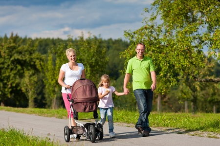 walking down: Family with two children (the baby lying in a baby buggy) walking down a path outdoors