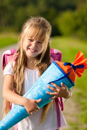 enrollment: Proud kid having first day at school holding a traditional cone filled with sweet stuff