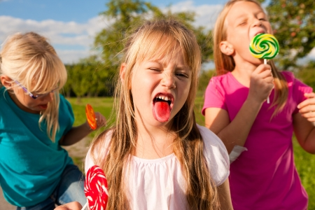 sticking: Three girls eating lollipops, the girl in front sticking her tongue out Stock Photo