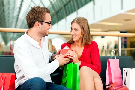 Couple - man and woman - in a shopping mall with colorful bags, he has bought a present for his wife or girlfriend, she is surprised photo