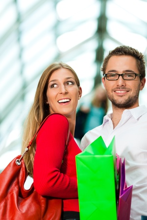 Couple - man and woman - in a shopping mall with colorful bags on an escalator photo