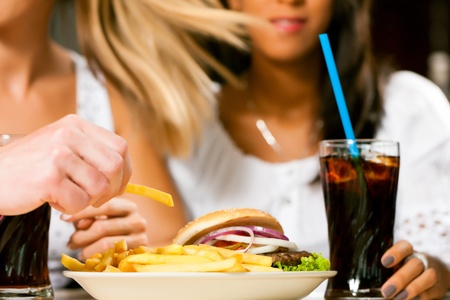 unhealthy lifestyle: Two women - one is African American - eating hamburger and drinking soda in a fast food diner; focus on the meal