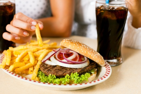 restaurant food: Two women - one is African American - eating hamburger and drinking soda in a fast food diner; focus on the meal