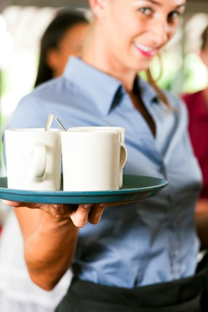 Woman as waitress in a bar or restaurant with coffee mugs; focus on the mugs and in the background are guests photo
