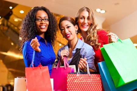Group of three women - white, black and Asian - shopping downtown in a mall Stock Photo - 10718762
