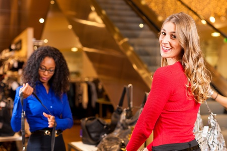 Two women in a shopping mall downtown looking for bags   photo
