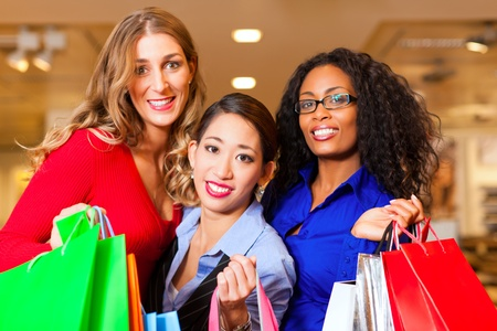 Group of three women - white, black and Asian - shopping downtown in a mall photo