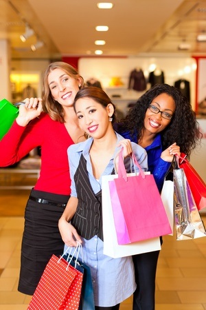 Group of three women - white, black and Asian - shopping downtown in a mall Stock Photo - 10718170
