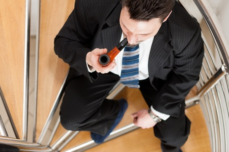closing time: Businessman sitting on the stairs in his apartment with pipe