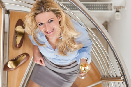 telecommuter: Businesswoman drinking champagne and sitting on the stairs in her apartment