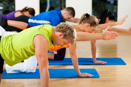 training group: Group of five people is doing stretching exercises in fitness club on gym mats