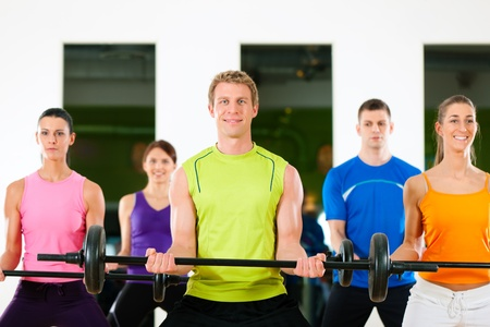 barbell: Group of five people exercising using barbells in gym or fitness club to gain strength and fitness