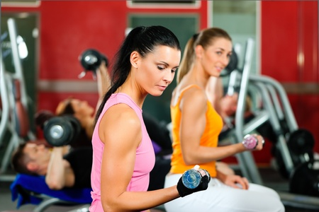 man lifting weights: People in gym or fitness club exercising with weights together