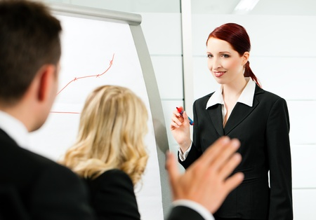 Business - presentation within a team; a female colleague is standing on the flipchart photo