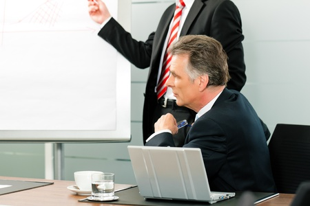 Senior Manager or boss in meeting discussing new strategy while a male colleague is doing the presentation photo