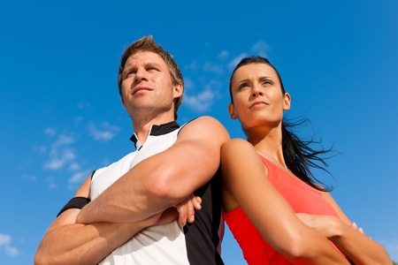 self confident: Fitness - Young sportive couple in front of a blue sky on a beautiful summer day outdoors Stock Photo