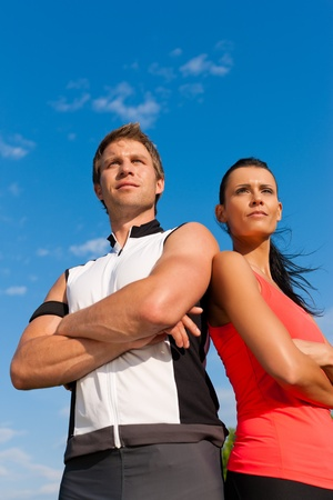 sportive: Fitness - Young sportive couple in front of a blue sky on a beautiful summer day outdoors Stock Photo