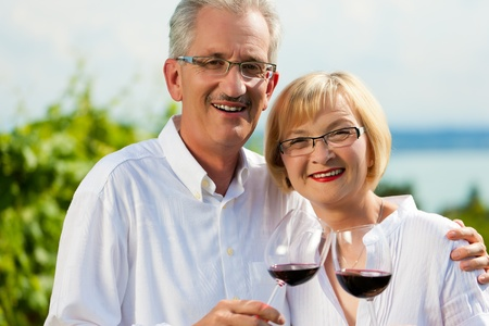 Happy mature couple - senior people (man and woman) already retired - drinking wine at lake in summer photo