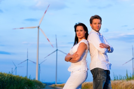 Young and powerful couple in front of windmill in summer photo