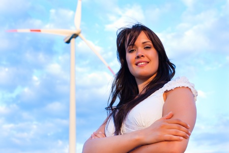 Young woman standing in front of windmill and the blue sky photo