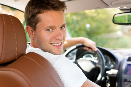test drive: Driver is sitting in his car or van and is driving - he is looking back Stock Photo