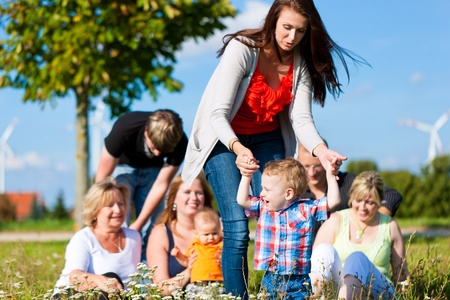 Family and multi-generation - mother, father, children and grandmother having fun on meadow in summer Stock Photo - 10718647