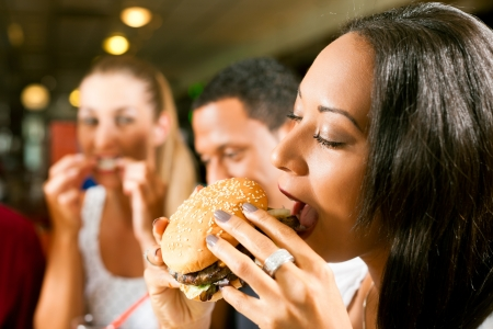 woman eat: Friends - one couple is African American - eating hamburger and drinking soda in a fast food diner; focus on the woman in front