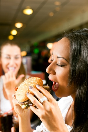 Friends - one couple is African American - eating hamburger and drinking soda in a fast food diner; focus on the woman in front photo