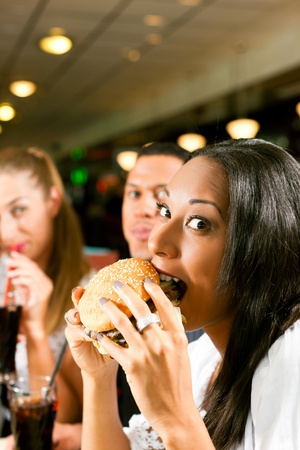 Friends - one couple is African American - eating hamburger and drinking soda in a fast food diner; focus on the woman in front Stock Photo - 10718719