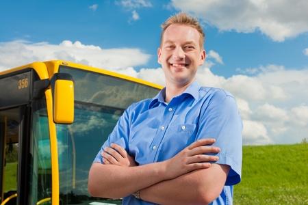 chofer de autobus: Conductor de autobús es pie frente a su autobús bajo al azul cielo