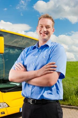 chofer de autobus: Conductor del autobús se encuentra delante de su autobús bajo al cielo azul