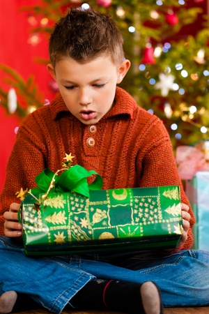 opening party: Christmas - happy little boy with Xmas present on Christmas Eve