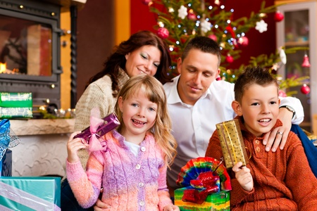 opening party: Christmas - happy family (parents with son and daughter) with gifts on Xmas Eve