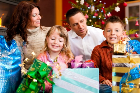 unwrapping: Christmas - happy family (parents with son and daughter) with gifts on Xmas Eve