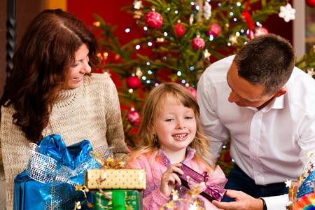 Christmas - happy family (parents with daughter) with gifts on Xmas Eve photo